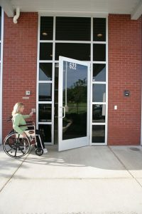 Woman in wheelchair using handicap door opener from Texas Access Control