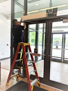 Texas Access Controls employee does maintence on an automatic door