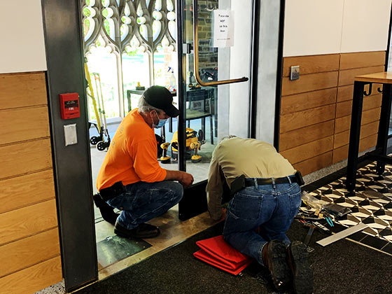 commercial door installation by 2 service people of Texas Access Controls